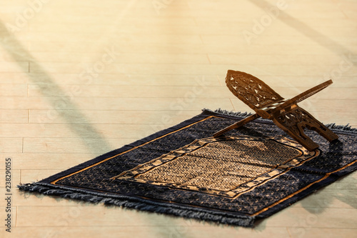 Rehal on Muslim prayer mat indoors. Space for text