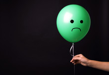 Woman Holding Balloon With Sad Face On Black Background, Space For Text. Threat Of Depression