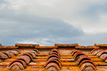 Old Ceramic Tiles Roof With Lichens And Clouds Above As Background (with Copy Space)