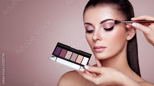 Makeup Artist applies Eye Shadow. Beautiful Woman Face. Perfect Makeup. Make-up