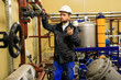 Technician engineer opens gate valve of pipeline on oil refinery
