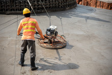 Construction Worker Wear Standard Safety Uniform Pouring And Leveling Fresh Concrete At Construction Site