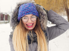 Beautiful Happy Girl In The Cold In A Blue Hat And Round Glasses.