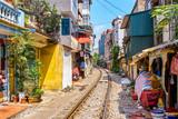 Fototapeta Uliczki - Hanoi city railway Perspective view running along narrow street with houses in Vietnam