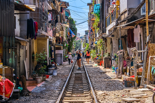 Woman is making a picture of Hanoi city railway Perspective view running along narrow street with houses in Vietnam