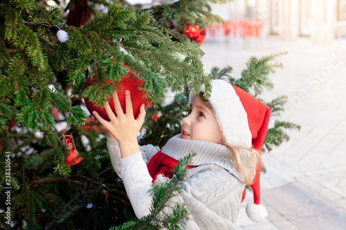 Decorating Christmas Trees Outside.Cute Child Girl Is Decorating Christmas Tree With Red