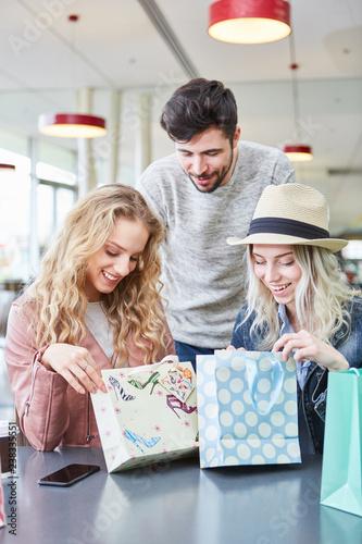 Cuadros en Lienzo Freunde schauen neugierig in ihre Einkaufstüten