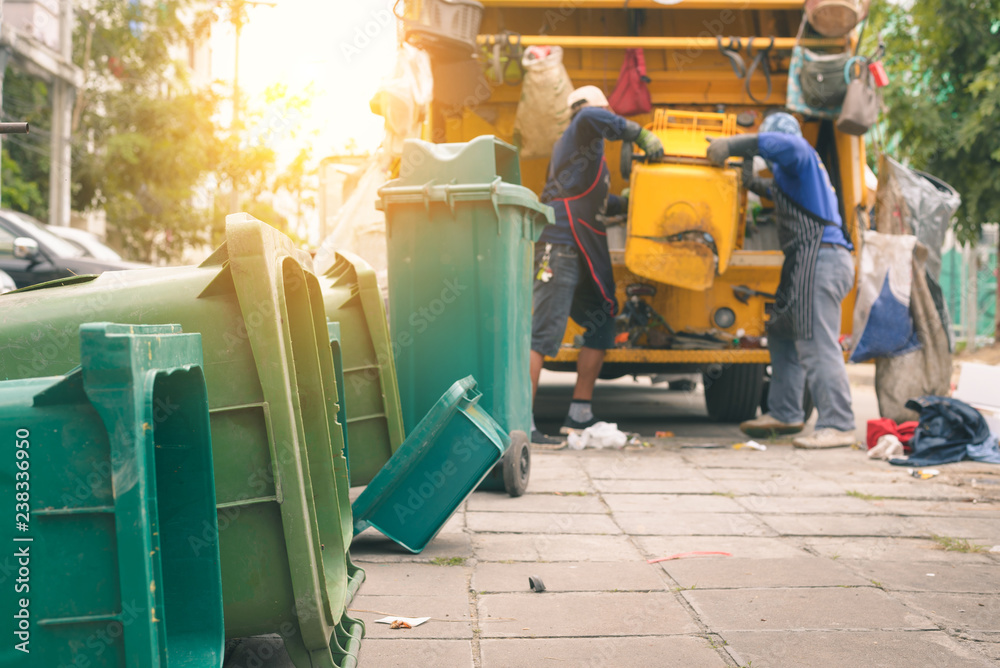 Fototapeta Garbage collector on the garbage truck.Sweeper or Worker are loading waste into the garbage truck carrier.