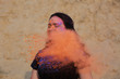 Merry young model having fun in a cloud of orange dry powder, celebrating Holi colors festival at the desert