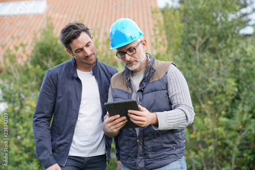 Builder going through outdoor plans with homeowner