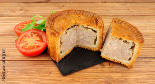 Crusty savoury pork meat pie on a wood background