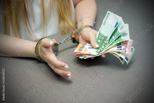 Fotografía  Office worker in handcuffs holding a bribe of euro banknote