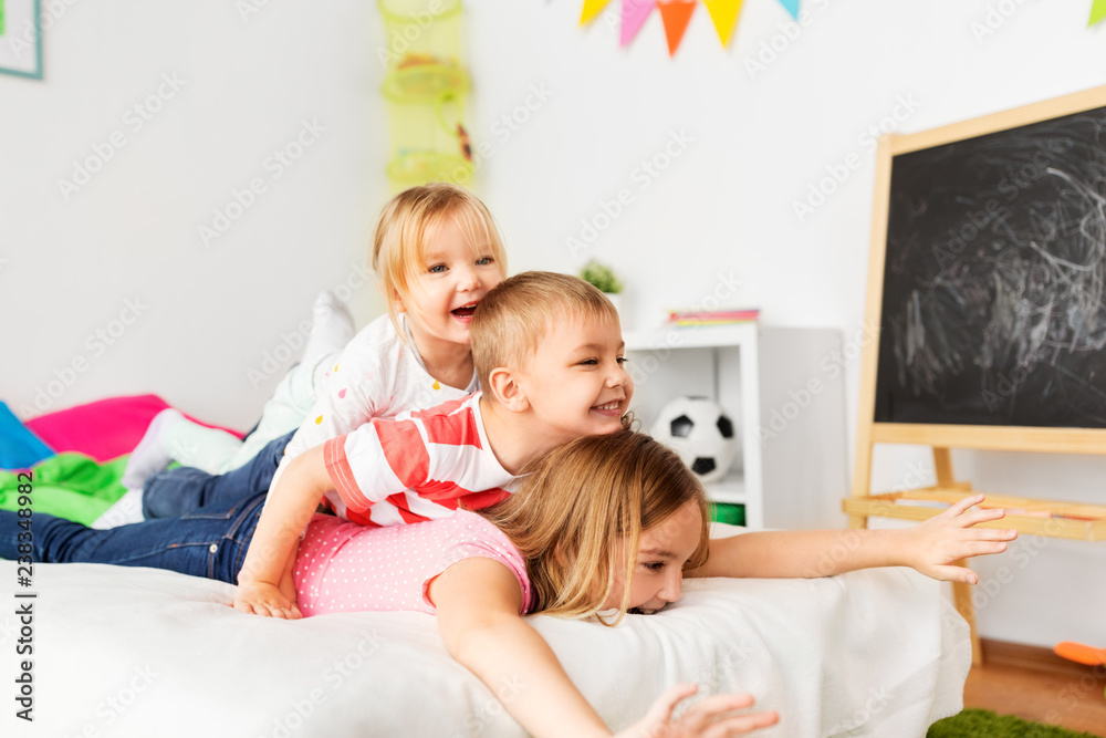 Fototapety, obrazy: childhood, leisure and family concept - happy little kids having fun in bed at home