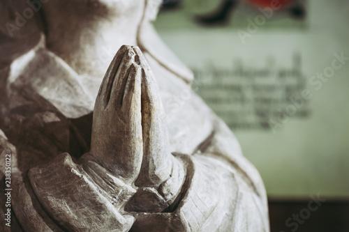 Fotografie, Obraz  Close up sur des mains en prière, statuette religieuse