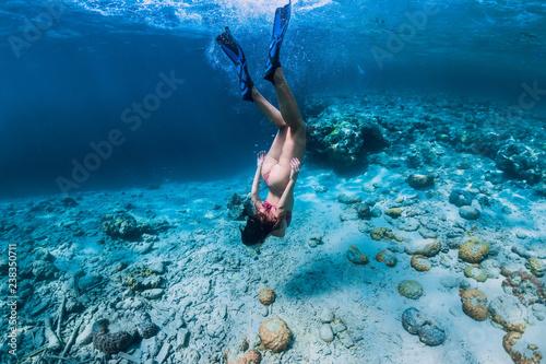Fotografía Woman free diver in bikini swim to deep in the tropical blue ocean