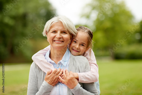 Fotografiet family, leisure and people concept - happy granddaughter hugging her grandmother