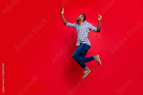 plakat Full length body size profile side view of nice funny crazy handsome cheerful guy wearing checkered shirt holding in hands cell reading text going in air isolated on bright vivid shine red background