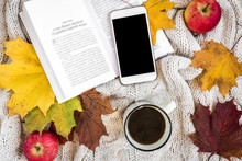 Book, Autumn Leaves, Apples, Mug Of Coffee And Mobile Phone On Knitted Plaid. Hello Autumn Concept.