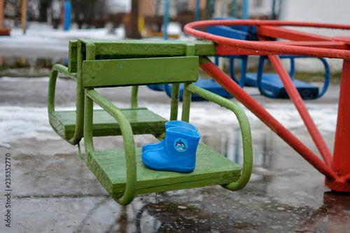 Fotografie, Obraz  Голубые резиновые сапожки на фоне зимней слякоти