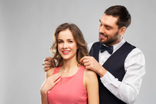 Couple, Jewelry And People Concept - Happy Man Puts Necklace With Diamond Pendant On His Girlfriend Over Grey Background