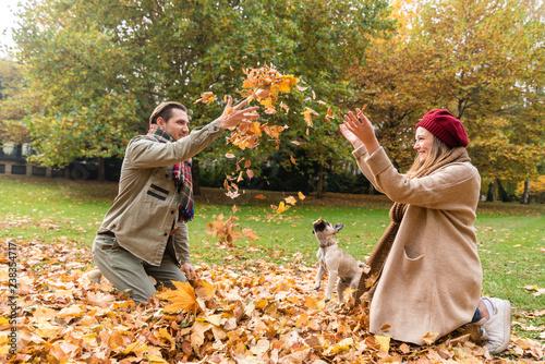 Fotografie, Obraz  Paar aus Frau und Mann spielt mit ihrem Hund im Herbst