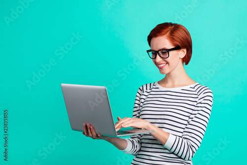 Pretty beautiful nice cheerful friendly kind adorable charming smart clever curious with short haircut lady user using holding netbook notebook on hand isolated vivid teal background