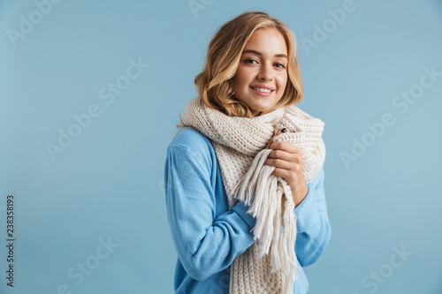 Image of blond woman 20s wrapped in scarf smiling at camera, isolated over blue background
