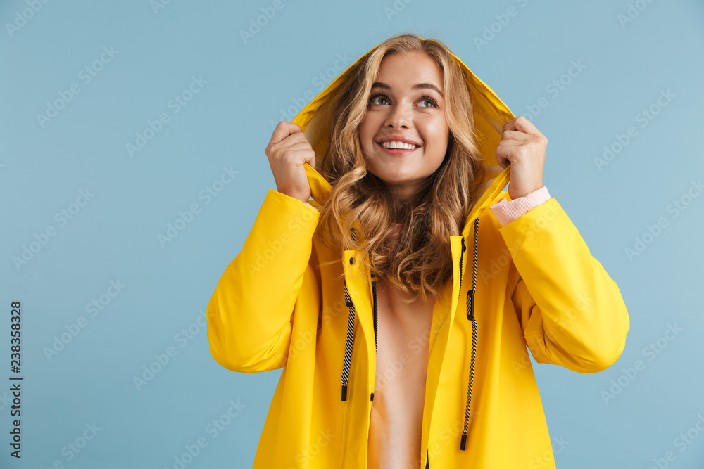 Fototapety, obrazy: Image of caucasian woman 20s wearing yellow raincoat smiling at camera, isolated over blue background