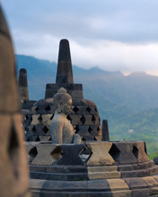 A Buddha Stone Statue Enshrined Into A Bell Shaped Stupa Looks Over The Valley On Top Of Buddhist Temple Of Borobudur, A Tourist Attraction In Central Java, Indonesia.