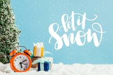 "Close-up Shot Of Christmas Gifts With Alarm Clock And Miniature Christmas Tree Standing On Snow On Blue Background With ""let It Snow"" Lettering"
