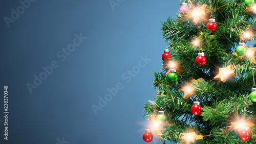 Christmas tree part with shiny decorations, blue background