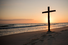 A Christian Holy Cross Standing On The Horizon Of Light And Sea