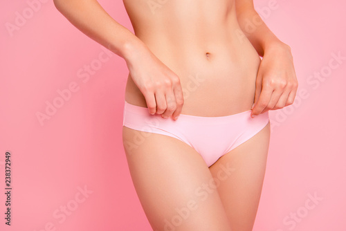 Obraz Cropped close up photo of touching with hands soft nice beautiful attractive silky hips legs abdomen weightloss advertising she her woman in pants isolated on rose background - fototapety do salonu