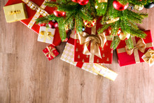 Top View Composition Of Christmas Tree Branches With Stack Of Different Presents In Colorful Festive Wrapping Tied With Bow. Pile Of Gifts Under Spruce Tree On Wooden Floor. Background, Copy Space.