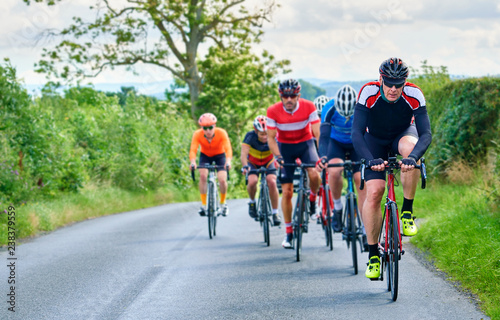 Foto op Aluminium A group of cyclists on a bike race on a sunny day along country roads in the UK.
