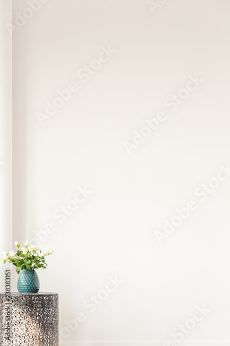 Copy space on empty white wall of elegant living room, coffee table with vase with flowers in the corner Wall mural