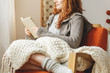 canvas print picture - Woman with blanket on knees sitting on armchair and reading book