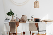 Natural Dining Room With Linen Napkins, White Tablecloth And Wicker Lamp
