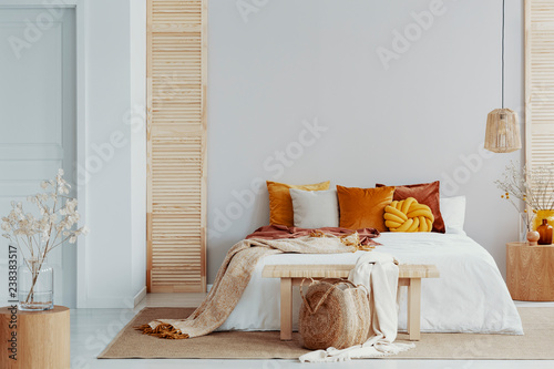 Tablou Canvas Brown and orange pillows on white bed in natural bedroom interior with wicker la