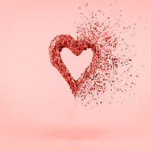 Glitter Heart Dissolving Into Pieces On Pink Background.  Valentines Day, Broken Heart And Love Emergence Concept . Living Coral Theme - Color Of The Year 2019