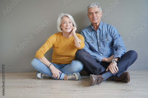 Full length of casual modern senior couple sitting on floor on background Tableau sur Toile