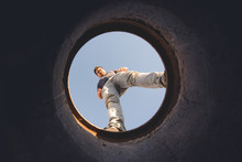 Man Looking Through Hole