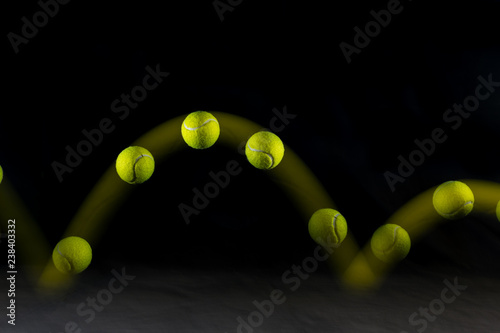 Movement or bounce of tennis ball isolated on black background. Wallpaper Mural