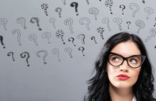 Small Question Marks With Young Businesswoman In A Thoughtful Face