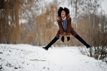 Curly Hair African American Woman Wear On Sheepskin Coat And Gloves Posed At Winter Day, Having Fun And Jump.