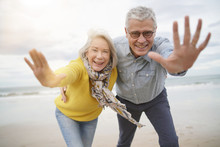 Playful Carefree Senior Couple On Beach Looking At Camera