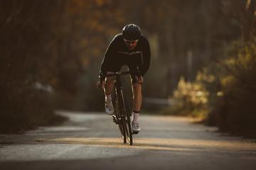 Profesionalni cestovni biciklistički trkač u akciji. Muškarci bicikliraju gorskim cestovnim biciklom u zalazak sunca.