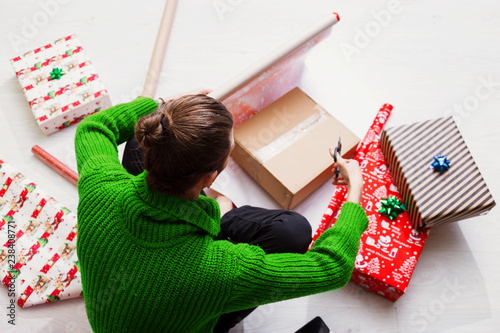 Top view of Man Wrapping Christmas Gifts At Home. Young man wearing green warm knitted sweater and wrapping gifts sitting on the floor. & Top view of Man Wrapping Christmas Gifts At Home. Young man wearing ...