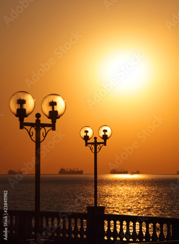 Fotografía  Scenic view of waterfront with lanterns backlit by setting sun and with ships in the roadstead