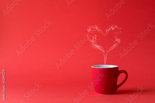 Cup of tea or coffee with steam in one heart shape on red background. Valentine's day celebration or love concept. Copy space